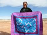 Glenna Begay holding her quilt